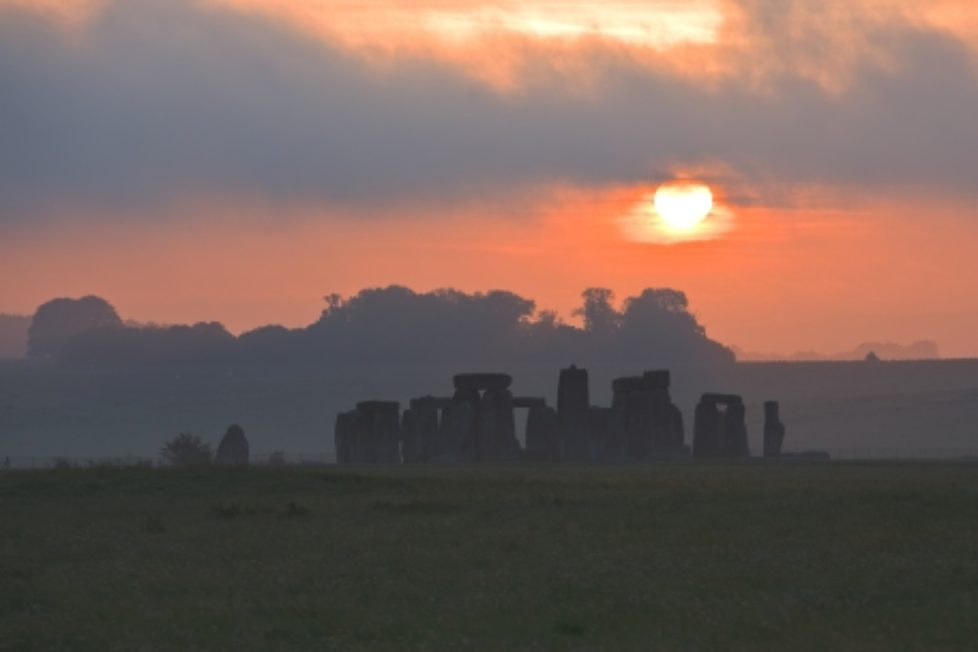 The sun rises behind the famous landmark of Stonehenge.